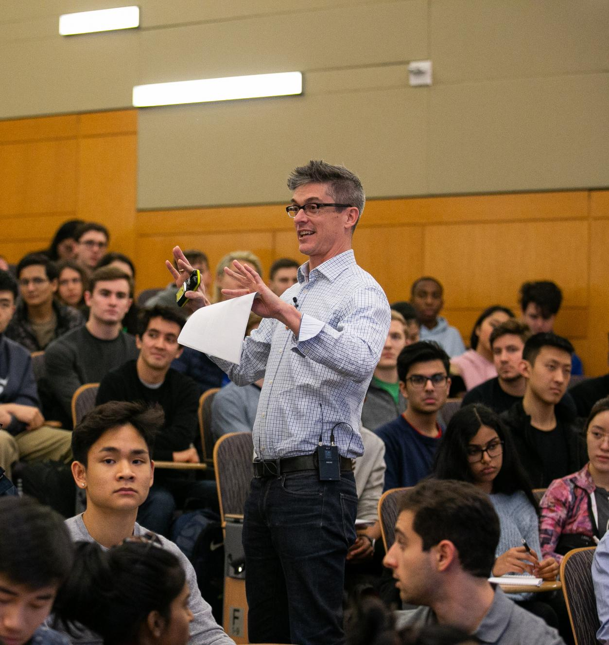 Professor speaking while standing in a crowd of seated students