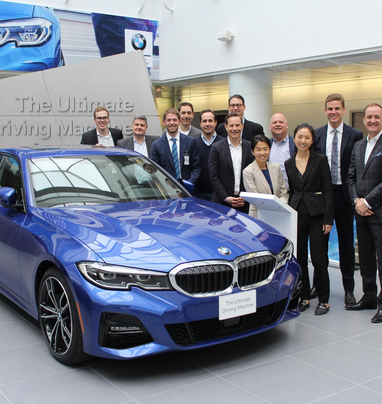 A smiling group of people standing beside a blue car
