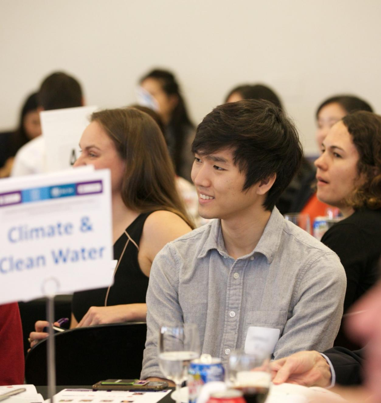 Young man in focus sitting at a table with a sign reading Climate & Clean Water.
