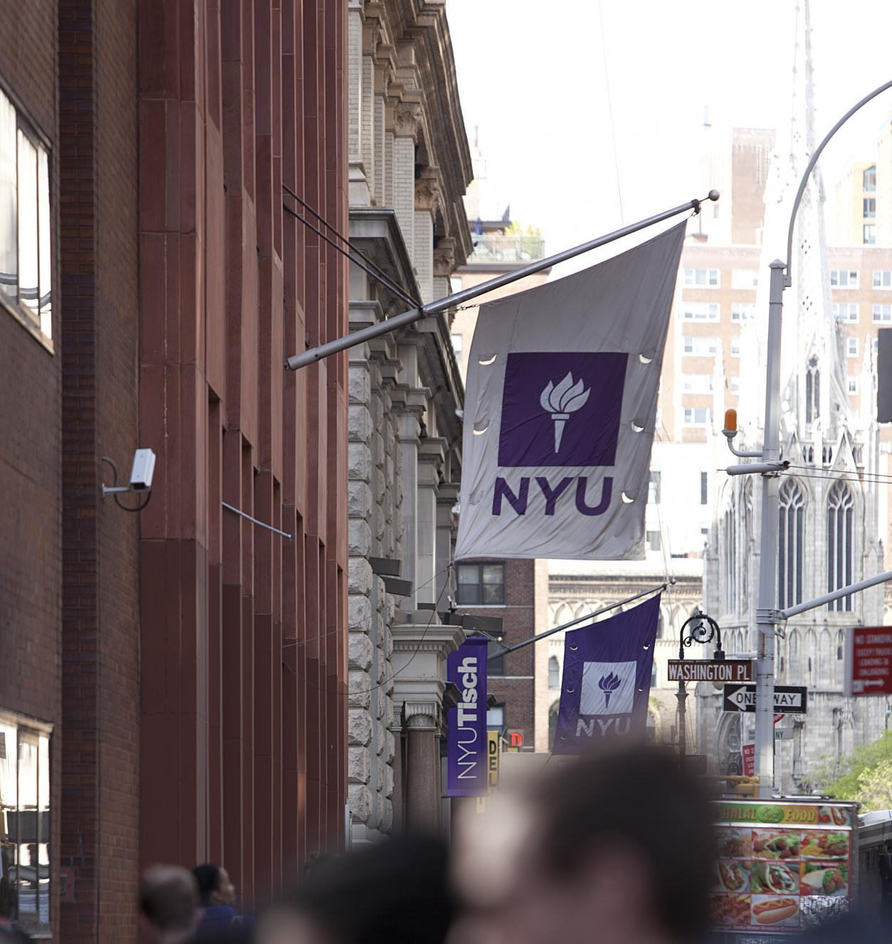 View of sidewalk with blurry crowds below an NYU Banner