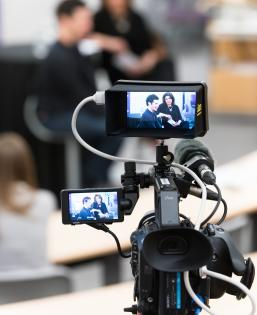 Close up of a camera filming two people in an interview