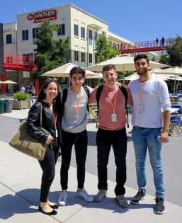 Four students standing next to each other at an outside plaza in San Francisco