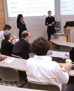 Two presenters stand in a classroom giving a workshop to faculty