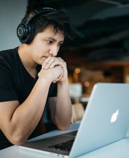 Student wearing headphones looks at a laptop
